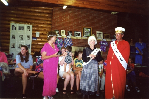 Anne LaCroix visits with Thelma and John McLain, costume contest winners, in front of the auction items during the 2000