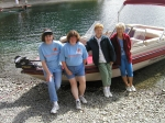 Mary Ann Moog, Lois Evans, Thelma McLain, and Ann LaCroix stroll along the lake and take a rest near a clan boat.